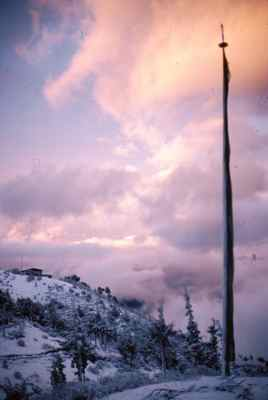 A Prayer Flag and Snow Greets the Sunrise in Bhutan
